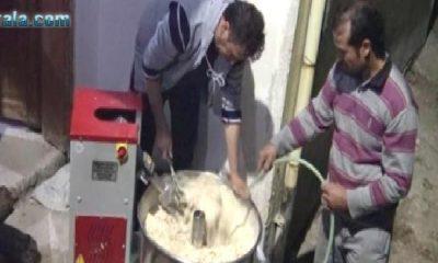 Muhtar, yaşlı kadınların kışlık ekmek hamurunu yoğuruyor